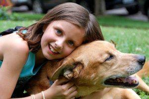 כלבים לילדים - ילדה מחבקת את הכלב שלה