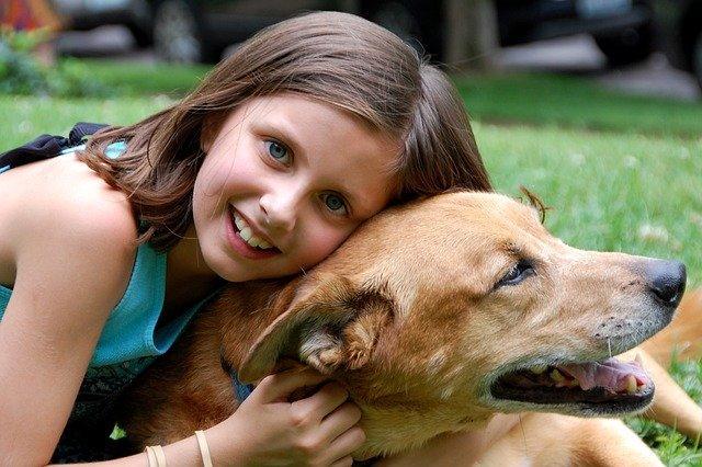 כלבים מומלצים לילדים - ילדה מחבקת את הכלב שלה